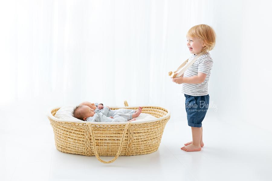 toddler taking photograph of twin newborns