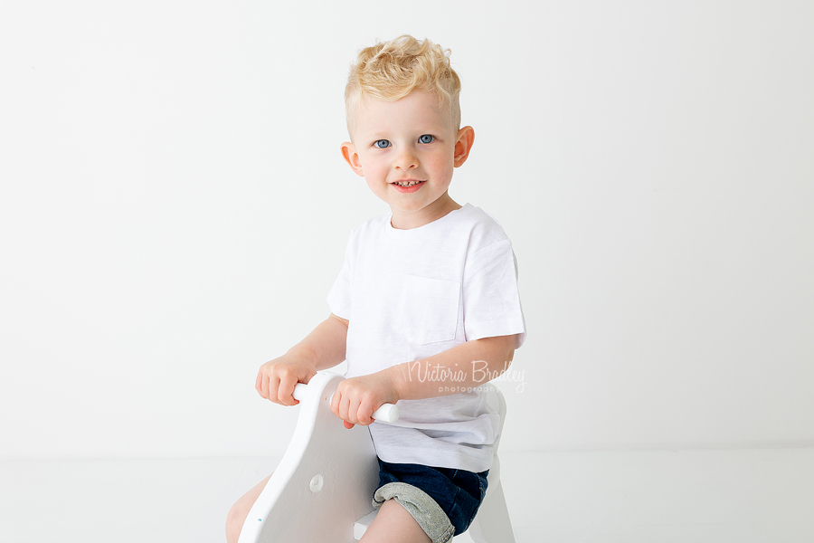 close up of 2 year old boy on rocking horse