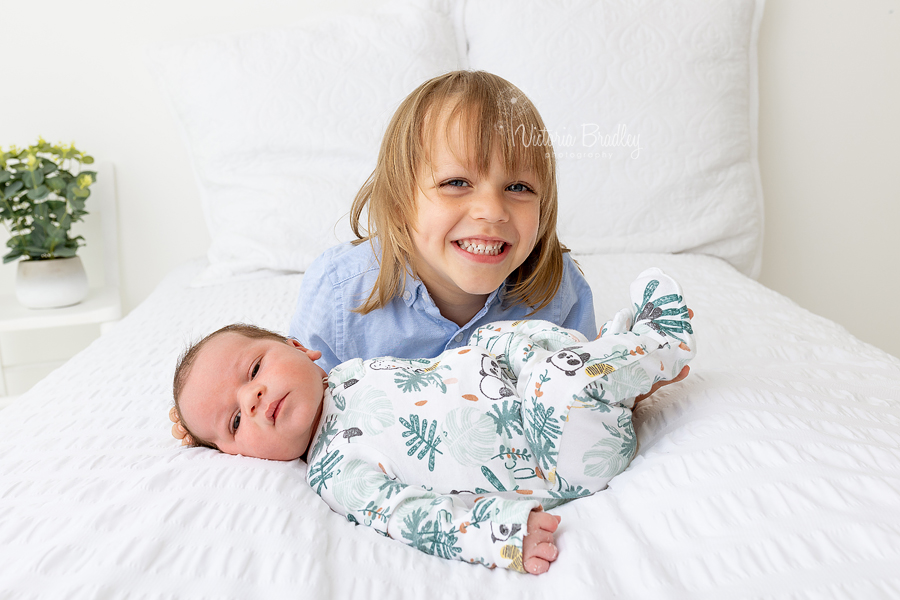sibling and newborn on white bed