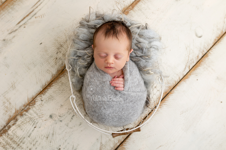 wrapped baby girl in grey, new born
