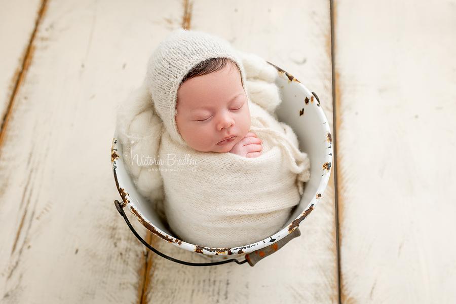 wrapped newborn in cream bucket