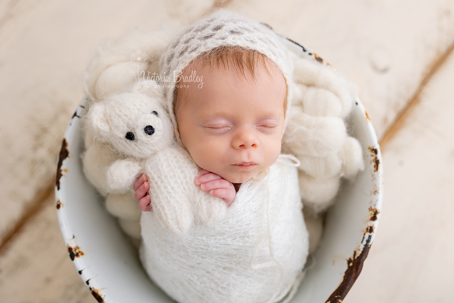 wrapped newborn with small teddy