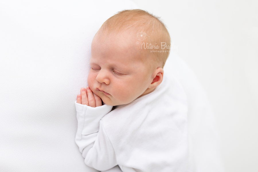 sleepy newborn on white