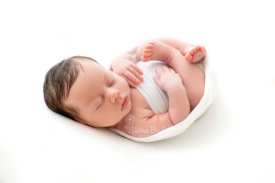 wrapped newborn on white