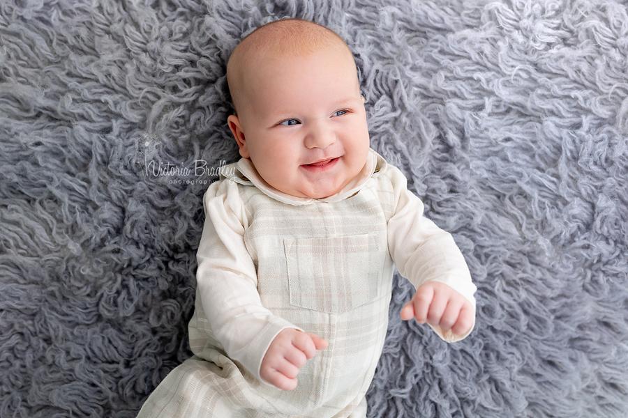 smiley baby on grey rug