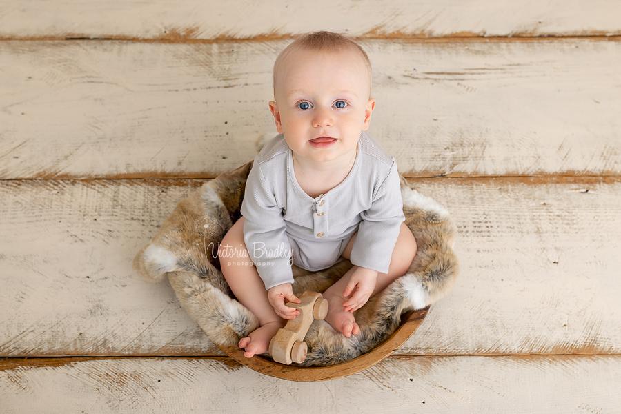 baby sat in wooden bowl