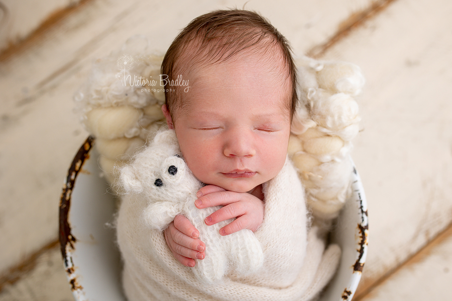 newborn holding teddy