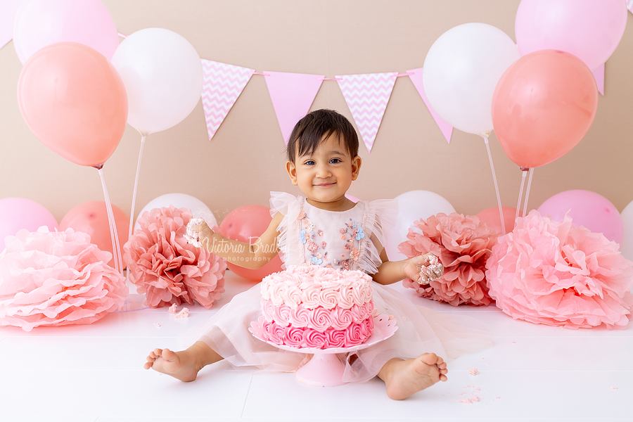 smiling baby girl with pink cake