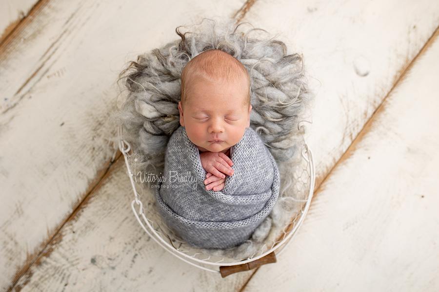 wrapped newborn boy in grey in basket