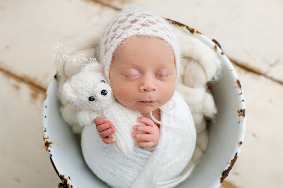 wrapped newborn in white with teddy