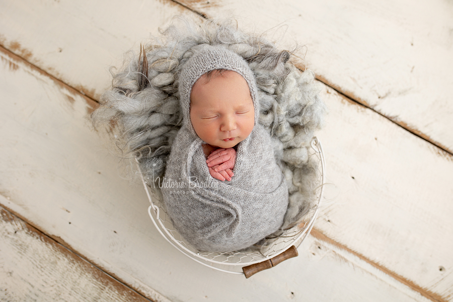 wrapped newborn on grey